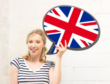 english flag: education, fogeign language, english, people and communication concept - smiling woman holding text bubble of british flag