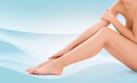 naked woman sitting: healthcare, beauty and people concept - beautiful woman touching her bare legs over blue waves background