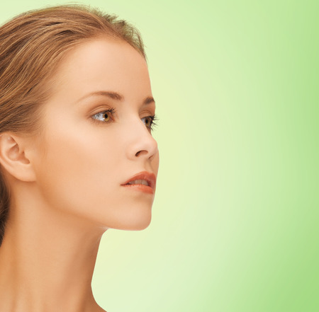 natural looking: beauty, people and health concept - beautiful young woman face over green  Stock Photo