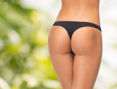 beauty, people and body care concept - close up of female legs in black bikini panties over green  Banque d'images