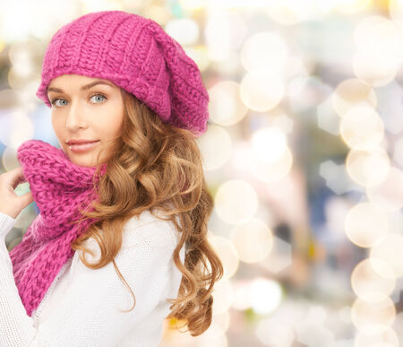 pink hat: happiness, winter holidays, christmas and people concept - young woman in pink hat and scarf over lights  Stock Photo