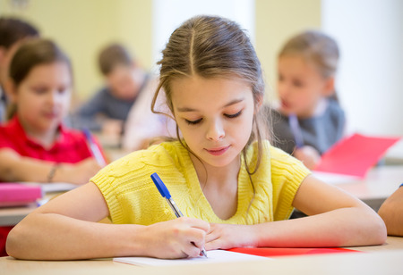 preteen girl: education, elementary school, learning and people concept - group of school kids with pens and notebooks writing test in classroom