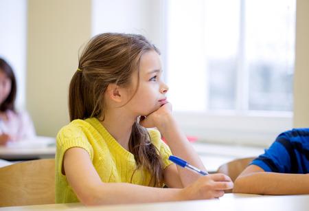 salon de clase: educaci�n, escuela primaria, el aprendizaje y el concepto de la gente - ni�a de la escuela con la pluma que se aburre en clase