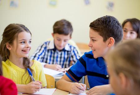 educación, escuela primaria, el aprendizaje y el concepto de la gente - grupo de niños de la escuela con lápices y cuadernos de escritura de prueba en el aula Foto de archivo