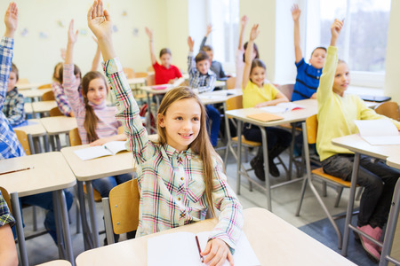 education, elementary school, learning and people concept - group of school kids with notebooks sitting in classroom and raising hands Standard-Bild