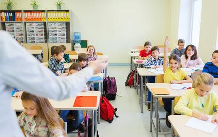 onderwijs, basisschool, leren en mensen concept - groep schoolkinderen met leraar in de klas zitten en verhogen handen