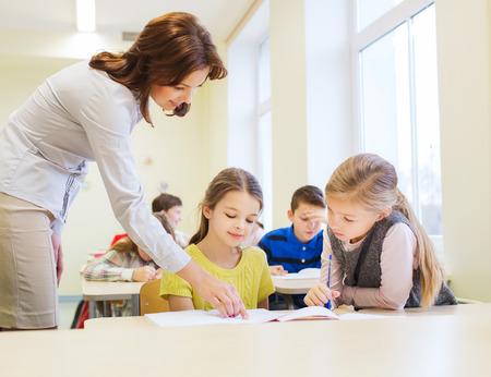vzdělávání, základní škola, učení a lidé koncept - učitel pomáhá školní děti ve třídě