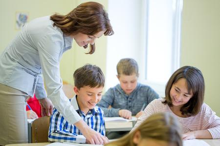 salon de clase: educaci�n, escuela primaria, el aprendizaje y el concepto de la gente - Profesor de ayudar a ni�os de la escuela de escritura de prueba en el aula Foto de archivo