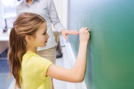 L'éducation, l'école primaire, l'apprentissage, les mathématiques et les gens notion - peu souriant écriture des nombres d'écolière sur le vert tableau noir dans la classe Banque d'images - 34752481