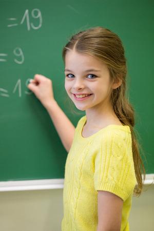 školačka: vzdělávání, základní škola, učení, matematika a lidé koncept - trochu s úsměvem čísla školačka psaní na zelené křída palubě ve třídě