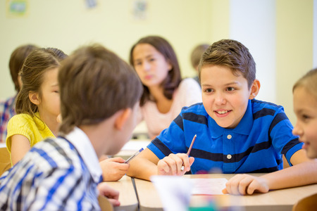 school of life: education, elementary school, learning and people concept - group of school kids talking during lesson in classroom Stock Photo