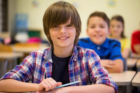学校を笑顔のグループ子供教室に座っている人々 のコンセプト - 学習、小学校教育