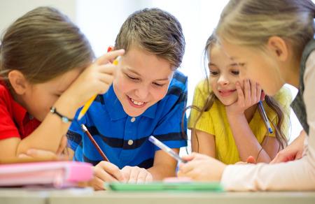 ni�os escribiendo: educaci�n, escuela primaria, el aprendizaje y el concepto de la gente - grupo de ni�os de la escuela con l�pices y papeles de escritura en el aula Foto de archivo