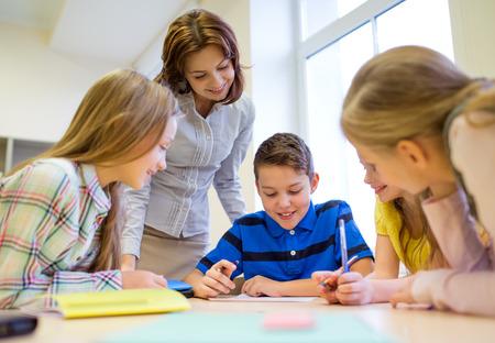 ni�os sonriendo: educaci�n, escuela primaria, el aprendizaje y el concepto de la gente - Profesor de ayudar a ni�os de la escuela de escritura de prueba en el aula Foto de archivo