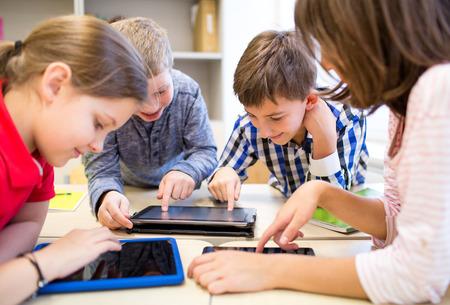 salon de clases: educación, escuela primaria, el aprendizaje, la tecnología y el concepto de la gente - grupo de niños de la escuela con la computadora Tablet PC que se divierte en descanso en el aula