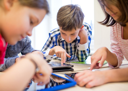 chicas guapas: educaci�n, escuela primaria, el aprendizaje, la tecnolog�a y el concepto de la gente - grupo de ni�os de la escuela con la computadora Tablet PC que se divierte en descanso en el aula