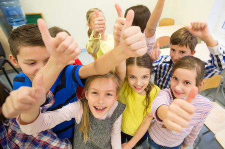 classroom: education, elementary school, learning, gesture and people concept - group of school kids and showing thumbs up in classroom