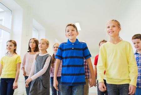 chicas sonriendo: educaci�n, escuela primaria, las bebidas, los ni�os y las personas concepto - grupo de ni�os de escuela sonriente caminando en el pasillo Foto de archivo