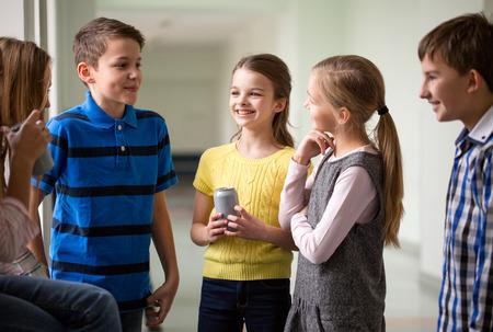 ni�os hablando: educaci�n, escuela primaria, las bebidas, los ni�os y las personas concepto - grupo de ni�os de la escuela con las latas de refrescos hablando en el pasillo Foto de archivo