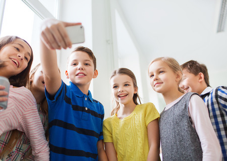 onderwijs, basisschool, drankjes, kinderen en mensen concept - groep schoolkinderen nemen Selfie met smartphone in de gang Stockfoto