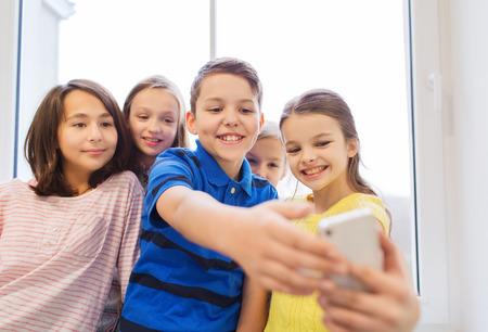 preteen boy: education, elementary school, drinks, children and people concept - group of school kids taking selfie with smartphone in corridor Stock Photo