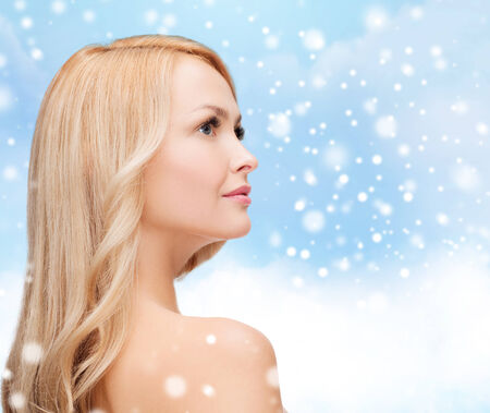 heath, people and beauty concept - beautiful young woman with bare shoulders over blue sky, snow and clouds background photo