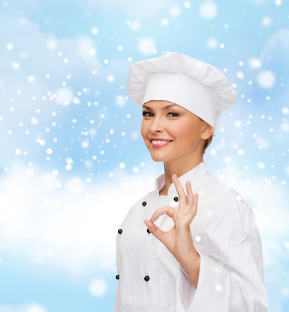 christmas cooking: christmas, cooking, profession, gesture and people concept - smiling female chef showing ok hand sign over blue snowy sky and cloud  Stock Photo