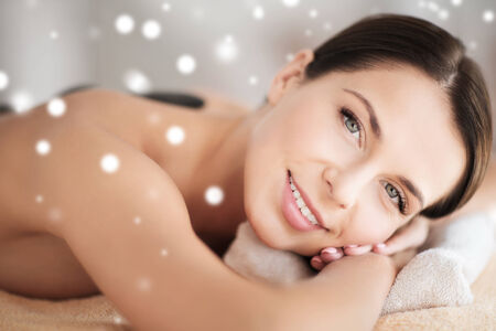 beauty, health, people and spa concept - beautiful young woman in spa salon lying on the massage desk photo