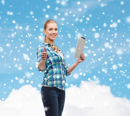technology, gesture and people concept - smiling girl with tablet pc computer showing thumbs up over blue snowy sky and cloud  photo