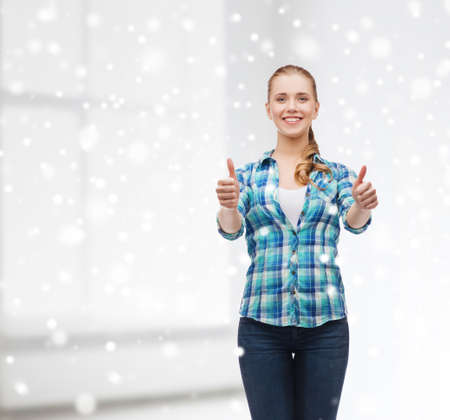 gesture, school and people concept - smiling student girl showing thumbs up over white room and snow  photo