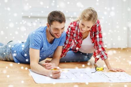 repair, building, renovation and people concept - smiling couple looking at blueprint at home photo