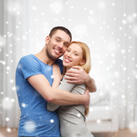 inlove: love, people and family concept - smiling couple hugging at home Stock Photo