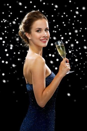 sektglas: Menschen, Urlaub, Luxus und Feier-Konzept - lächelnde Frau mit Glas Sekt über schwarz verschneiten Hintergrund Lizenzfreie Bilder