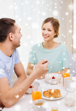 breakfast room: food, home, people and happiness concept - smiling couple having breakfast at home