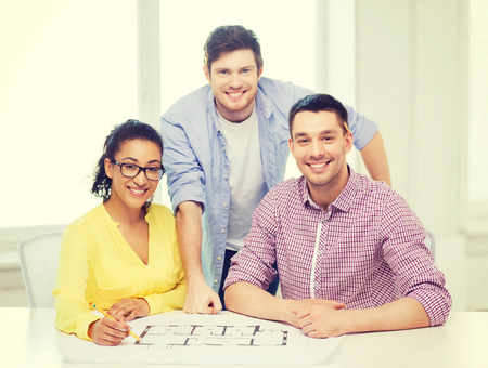 young group: startup, education, architecture and office concept - three smiling architects with blueprint working in office