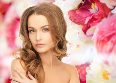 beauty, people and health concept - beautiful young woman with bare shoulders over pink floral photo