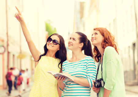 travel guide: tourism, travel, leisure, holidays and friendship concept - smiling teenage girls with city guide and camera outdoors
