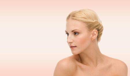 face side: beauty, people and health concept - beautiful young woman face over pink