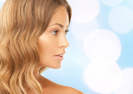 beauty, people and health concept - beautiful young woman face over blue lights