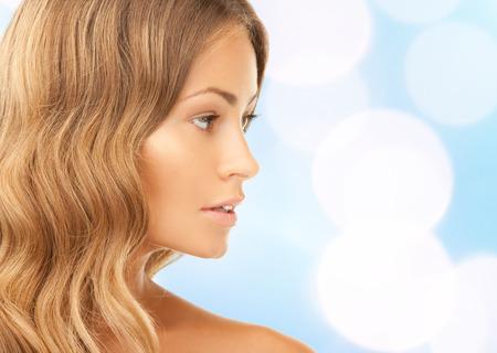 beleza, pessoas e conceito de saúde - belo rosto jovem mulher com mais de luzes azuis Imagens