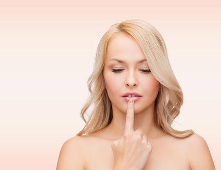 cold sore: health, people and beauty concept - beautiful young woman touching her lips over pink  Stock Photo