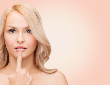 augmentation: health, people and beauty concept - beautiful young woman touching her lips over pink  Stock Photo