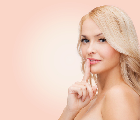 smooth hair: health, secret, people and beauty concept - clean face of beautiful young woman pointing finger to her lips over pink  Stock Photo