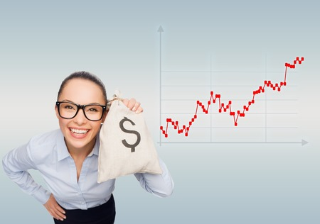forex: business, money and people concept - smiling businesswoman in eyeglasses holding money bag with dollar over gray background and forex graph