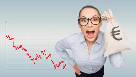 crisis economica: negocio, dinero y personas concepto - empresaria sorprendida en anteojos celebración bolsa de dinero con euro sobre fondo gris y el gráfico de divisas Foto de archivo