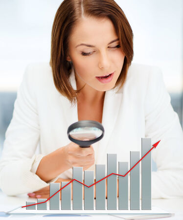 business, documents, statistics and people concept - businesswoman looking through magnifier to graphs in office photo