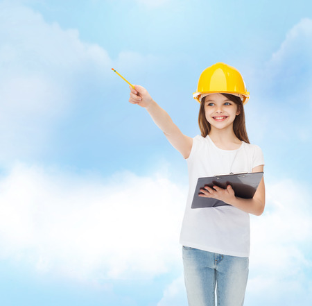 take a note: childhood, construction, architecture, building and people concept - smiling little girl in protective helmet with clipboard pointing pencil
