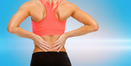 back ache: fitness, healthcare and medicine concept - close up of sporty woman touching her back
