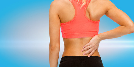 girls back to back: fitness, healthcare and medicine concept - close up of sporty woman touching her back