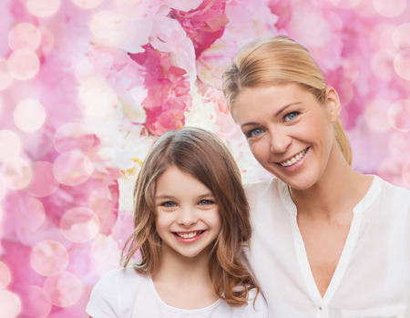 a generation: family, childhood, happiness and people - smiling mother and little girl over pink lights background